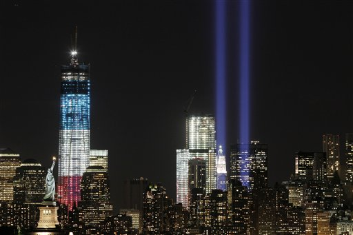The Tribute in Light shines above the World Trade Center and the Statue of Liberty, left, Monday, Sept. 10, 2012, as seen from Bayonne, N.J. Tuesday will mark the eleventh anniversary of the terrorist attacks of Sept. 11, 2001. The tallest tower is 1 World Trade Center, now up to 105 floors. In the center is 4 World Trade Center. (AP Photo/Mark Lennihan)